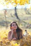 Mujer joven que comtempla en hojas Imagen de archivo libre de regalías