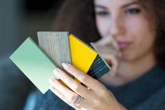 Mujer joven que comtempla muestras del color Imágenes de archivo libres de regalías