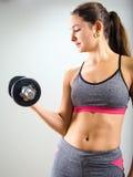 Mujer joven que concentra en rizo de la pesa de gimnasia Imagenes de archivo