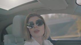Mujer joven que conduce el coche almacen de metraje de vídeo