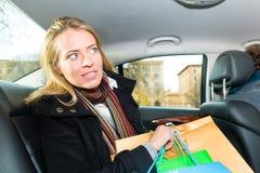 Mujer que conducía en taxi, ella hacía compras fotografía de archivo