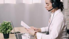 Mujer joven que conduce la consulta en línea mientras que en oficina