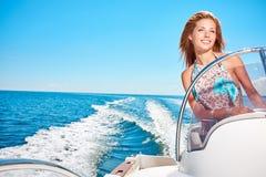 Mujer joven que conduce un barco de motor Fotografía de archivo