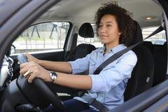 Mujer joven que conduce un coche Imágenes de archivo libres de regalías