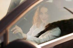 Mujer joven que conduce un coche en la ciudad Retrato de una mujer de negocios hermosa en un coche Concepto del asunto fotografía de archivo