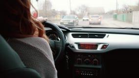 Mujer joven que conduce un coche, vista posterior almacen de metraje de vídeo