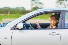 Mujer joven que conduce un coche y que usa el teléfono Fotos de archivo libres de regalías