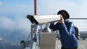 Mujer joven que considera a través del telescopio el punto de vista en las montañas metrajes