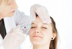 Mujer joven que consigue el botox en su ceño fruncido Fotografía de archivo libre de regalías