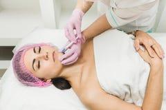Mujer joven que consigue la inyección cosmética en clínica de la belleza fotos de archivo