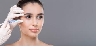Mujer joven que consigue la inyección facial de la belleza, panorama fotos de archivo