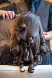 Mujer joven que consigue le el pelo hecho Fotografía de archivo