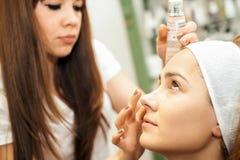 Mujer joven que consigue maquillaje hermoso foto de archivo libre de regalías