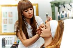 Mujer joven que consigue maquillaje hermoso imágenes de archivo libres de regalías