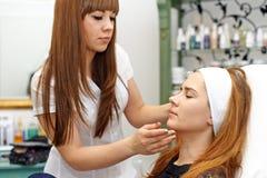 Mujer joven que consigue maquillaje hermoso fotografía de archivo libre de regalías