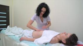 Mujer joven que consigue masaje anti profesional de las celulitis en el abdomen en salón del balneario almacen de metraje de vídeo