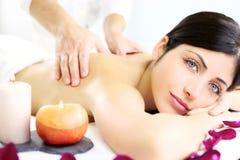 Mujer joven que consigue masaje posterior en balneario de lujo Foto de archivo libre de regalías