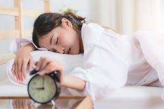 Mujer joven que consigue subrayada sobre despertar Fotografía de archivo libre de regalías