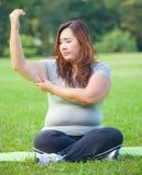 Mujer joven que controla su grasa del brazo Imagenes de archivo