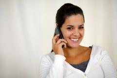 Mujer joven que conversa en el teléfono móvil que le mira Fotografía de archivo