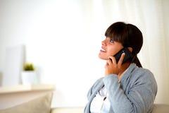 Mujer joven que conversa en el teléfono móvil que mira para arriba Fotos de archivo