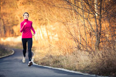 Mujer joven que corre al aire libre en un parque de la ciudad Imágenes de archivo libres de regalías