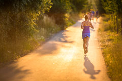 Mujer joven que corre al aire libre en una tarde soleada preciosa del verano Foto de archivo libre de regalías