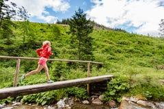Mujer joven que corre en el puente en montañas el día de verano Imagen de archivo
