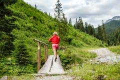 Mujer joven que corre en el puente en montañas el día de verano Fotografía de archivo