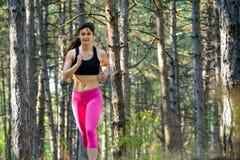 Mujer joven que corre en el rastro en el pino salvaje hermoso Forest Active Lifestyle Concept Espacio para el texto fotos de archivo libres de regalías