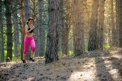 Mujer joven que corre en el rastro en el pino salvaje hermoso Forest Active Lifestyle Concept Espacio para el texto fotografía de archivo libre de regalías