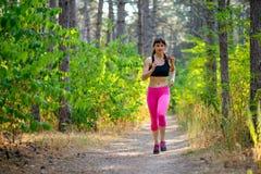 Mujer joven que corre en el rastro en Forest Active Lifestyle Concept salvaje hermoso Espacio para el texto foto de archivo libre de regalías