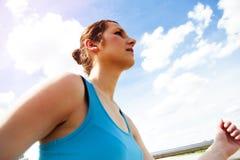 Mujer joven que corre en la ciudad sobre el brige en luz del sol foto de archivo