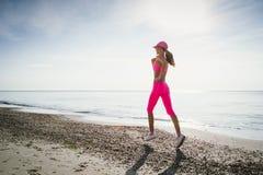 Mujer joven que corre en la costa de mar en la salida del sol o la puesta del sol imagen de archivo