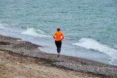 Mujer joven que corre en la playa báltica fotografía de archivo