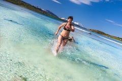 Mujer joven que corre en la playa del mar Imagen de archivo libre de regalías
