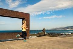 Mujer joven que corre en montañas en día de verano soleado imagen de archivo libre de regalías