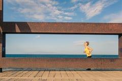 Mujer joven que corre en montañas en día de verano soleado imagen de archivo