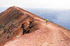 Mujer joven que corre en montañas en día de verano soleado fotos de archivo libres de regalías