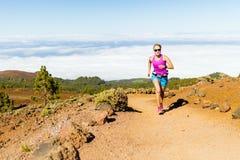 Mujer joven que corre en montañas en día de verano soleado fotos de archivo