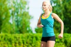 Mujer joven que corre en parque verde Foto de archivo libre de regalías