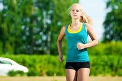 Mujer joven que corre en parque verde Imagen de archivo libre de regalías