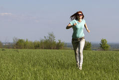 Mujer joven que corre en prado de la primavera Fotografía de archivo