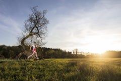 Mujer joven que corre en puesta del sol Imagen de archivo libre de regalías