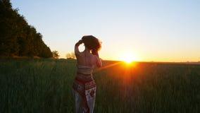 Mujer joven que corre feliz a través de un campo verde en la salida del sol, cámara lenta almacen de video