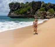 Mujer joven que corre a lo largo de la orilla del océano Imágenes de archivo libres de regalías