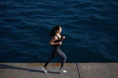 mujer joven que corre a lo largo de la playa con sorprender olas oceánicas grandes en fondo Imagen de archivo libre de regalías