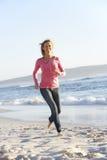 Mujer joven que corre a lo largo de Sandy Beach On Holiday Fotos de archivo libres de regalías