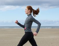 Mujer joven que corre por la playa Imagen de archivo