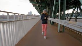 Mujer joven que corre sobre el puente industrial en la ciudad metrajes